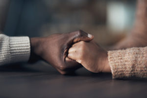 Cropped shot of two people holding hands; concept of support